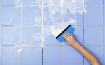 hand-spreading-grout-on-tiles-with-grout-spreader-80033352-583c5e073df78c6f6a2f22b6